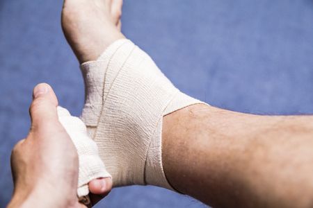 tensor: Sport injury shot. Sprained ankle. A leg tensor bandage being applied outdoors. Close up Shot