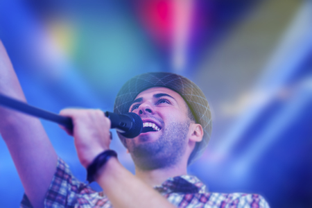 pop idol: Young man singing on stage in concert with lights in bacground