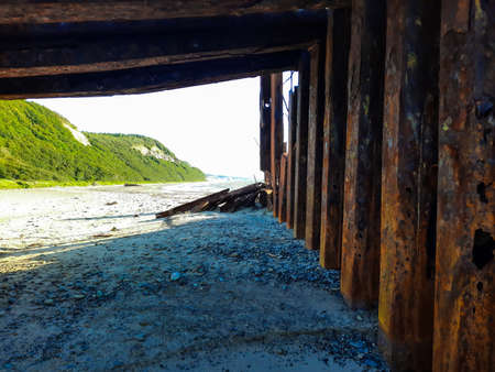 Beach under an old rusty bridge. Green mountains in the distance Stockfoto