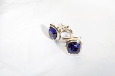 cuff links: Mens cuff links made of white metal with a blue stone on white background Stock Photo