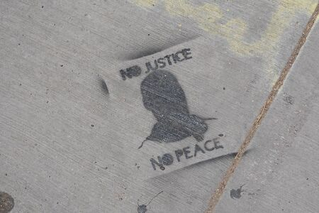 No justice no peace stenciled in spray paint on a sidewalk.