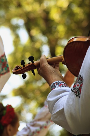 close-up man in traditional colorful costume with violine in hand