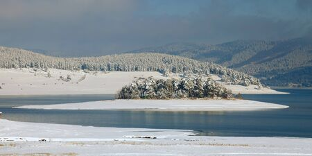 Unfrozen lake in the winter forests of Rhodopes, Bulgaria. Blue cold water and snow island photo