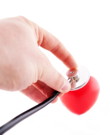 Hand with stethoscope taking diagnose on Red Heart, concept of care   photo