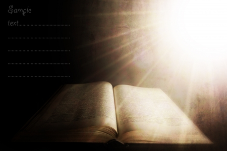 sanctification: holy light over the old book; vintage textured background with space for sample text
