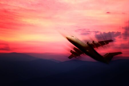 aeroplane flight in dramatic red sunset over the mountains photo