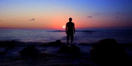 young man and sunrise on sea- panoramic view Stockfoto