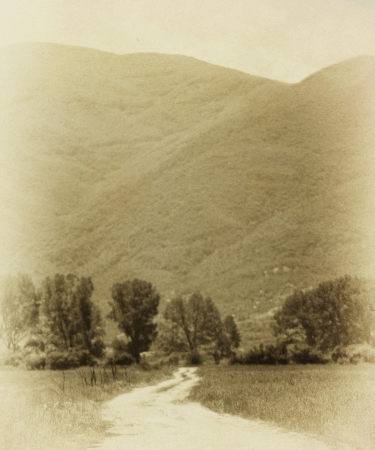 dirtroad: vintage dirt road in meadows near high mountain- textured old background