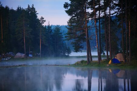 calm morning on the lake with smooth fog above the water photo