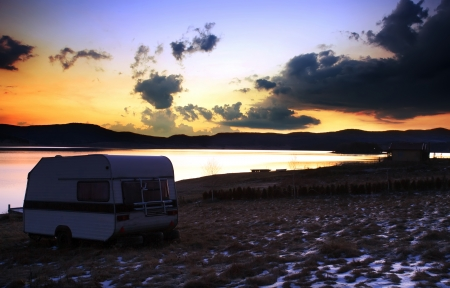 camper near lake in stunning HDR sunrise winter landscape  Stock Photo
