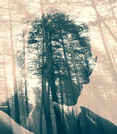 Abstract duotoned double exposure portrait of woman and black forest  Stock Photo