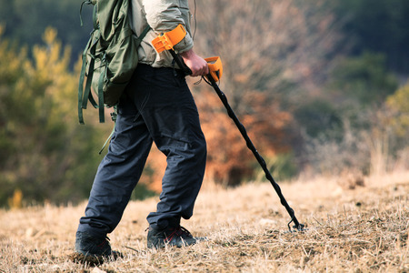man hunt treasure with metal detector in autumn forest