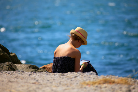 beautiful blonde girl with tablet on the beach, soft focused blue sea background  photo