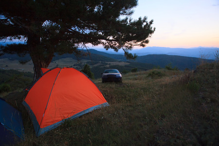 car and tent in high plase for camping sunset time with low light  photo
