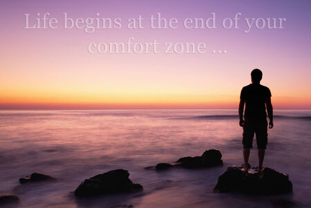 man on the edge on rock in calm sea sunrise, unknown inspirational quote above Stock Photo