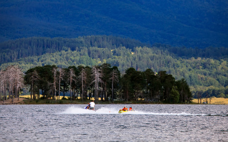 Jet skiing and draging small boat for fun of tourist in bulgarian lake  photo