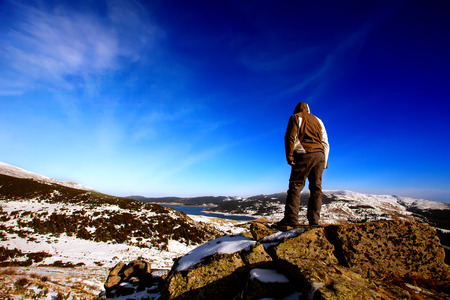 hiker on the top of the mountain, winter landscape in bulgarian Rila mountain  photo