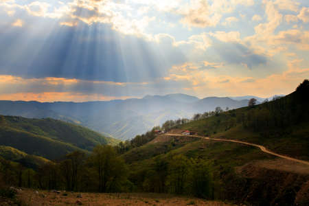 dirt road: Sunrays in sunset over the high mountain dirt road and small house in bulgarian mountains  Stock Photo