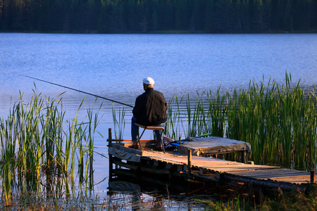 old man fishing from the key in high mountain blue lake, sunset golden hour  Stock Photo
