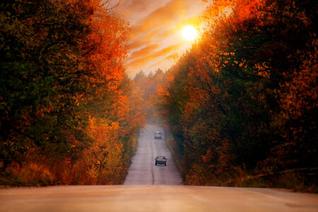 colorful HDR red sunset over the straight high mountain autumn road photo