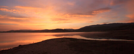 Burning sky sunset panorama on the high mountain lake photo