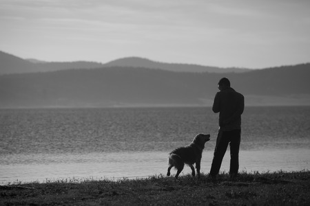 mountain dog: man and dog near high mountain lake in sunset time, black and white landscape