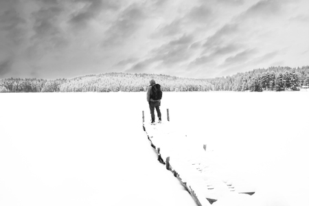 one lane street sign: Man stand on wooden bridge in winter mountains, high key black and white winter landscape