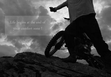 dirt bike: man on the edge on rock with dirt bike, unknown inspirational quote above