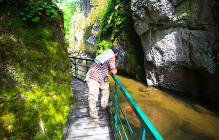 stay beautiful: man stay on eco road build by human near beautiful river in bulgarian mountains