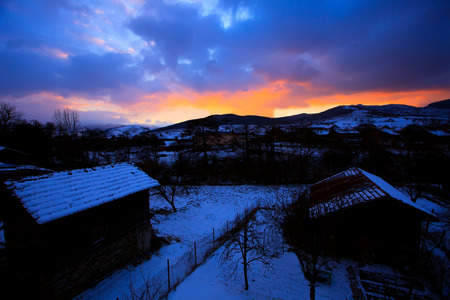contrasted: stunning high contrasted HDR sunst over the small village, red colors in the sky, dusk time close to night Stock Photo