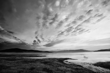 contrasted: black and white high contrasted sky above the mountain lake Stock Photo