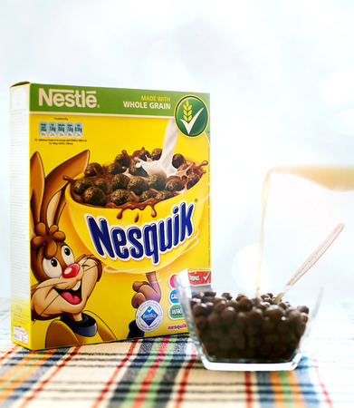 nestle: SOFIA , BULGAIRA  April 29, 2015: box Nesquick morning cereal and human hand with milk. Nesquick is made by Nestle the largest food company in the world measured by revenues and was founded in 1905
