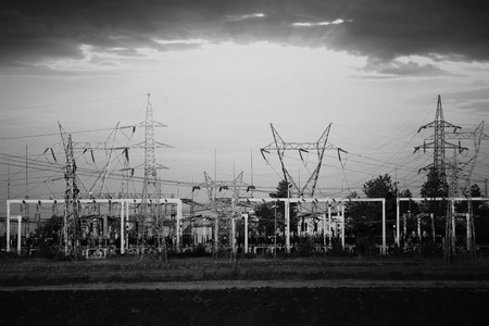 sub station: Sub electricity station with many pylons and dramatic sky in  black and white