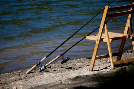 jigging: two rod for fishing over the wooden chair near blue lake