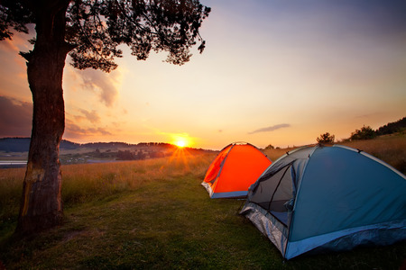camping: recreation area and camp with tent, sunset time with rising sun near hign mountain lake