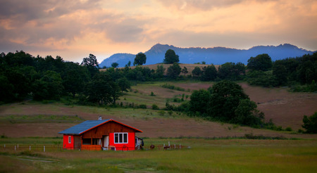 summer nature: red wooden villa in the fields, sunset time, HDR technique