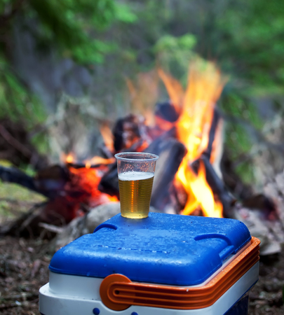 near beer: plastic cup full with beer near campfire