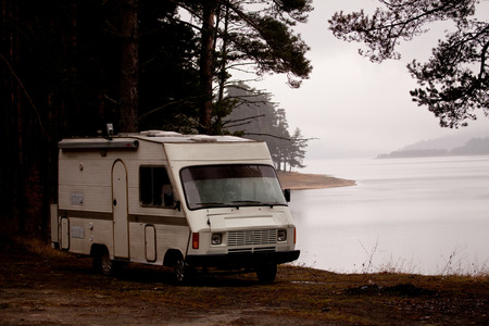 RV camper near lake in misty day