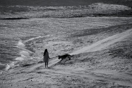 adn: paisaje blanco y negro con el hombre perro del ADN de caminar en la playa del lago Foto de archivo