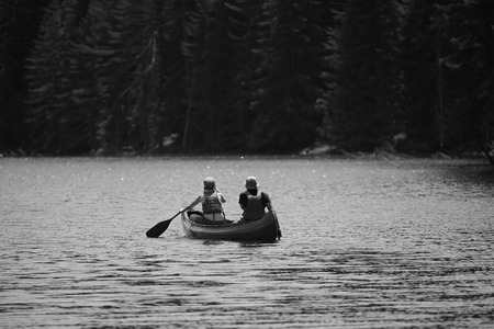 black white kayak: young couple with kayak in high mountain lake, black and white nature and human landscape