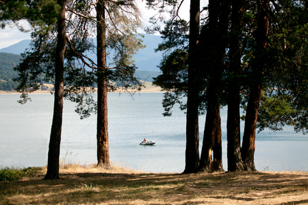 enchantment: man and boat fishing in high mountain lake, view from near forest
