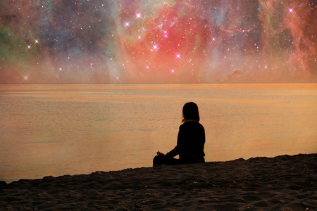 Follow your dreams, silhouette of woman meditaiting on the beach many stars above- elements of this image are furnished by NASA Stockfoto