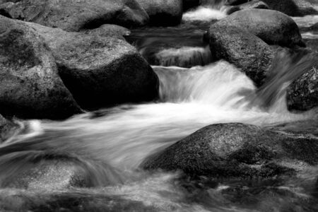 wild silky white: black and white details of high mountain river with big rocks Stock Photo