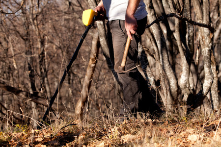 scavenge: man hunt treasure with metal detector in autumn forest