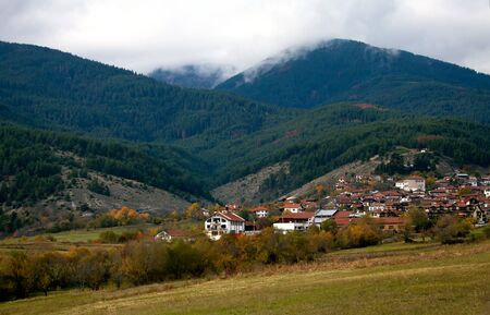 misty autumn day in bulgarian mountains, small village above