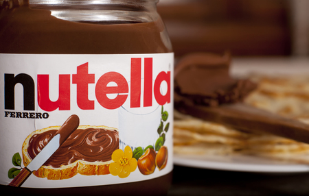 DORKOVO, BULGARIA - FEBRUARY 08, 2017: Close up Nutella jar and pankakes in the background.Nutella is the brand name of a chocolate hazelnut