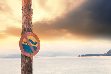 No swimming sign in front of dangerous lake, dramatic clouds behind Stock Photo