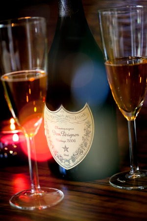 SOFIA, BULGARIA - OCTOBER 29, 2017: Dom Perignon Vintage 2006 champagne bottle and two glass, lights and bokeh from colorfull bar light Editorial