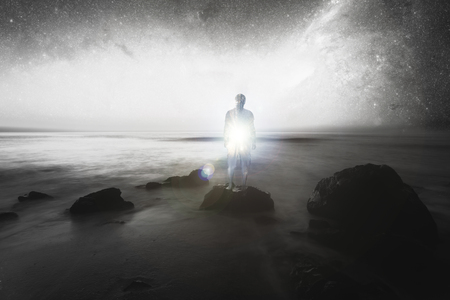 double exposure, man on the beach rocks, inside light, conceptual image, spiritual light