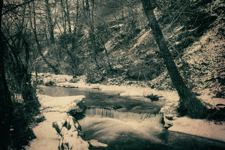 River running through the winter forest, vintage textured nature background